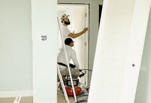 Two construction workers setting a door | Progress payments on construction projects