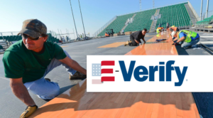 E-verify logo over image of construction workers in Florida stadium