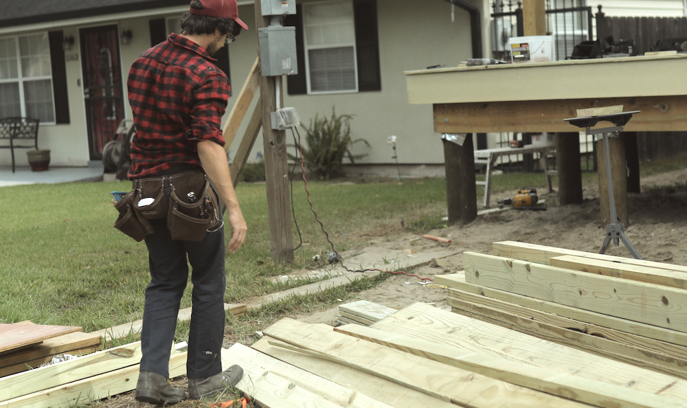 Contractor walks by lumber pile