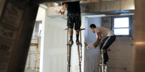 Subcontractors on stilts installing drywall