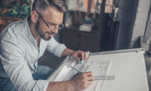 An architect looks at blueprints on a drafting table