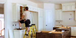 Contractor installing kitchen cabinets for a homeowner