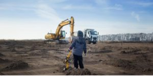 Worker looks across a field at construction equipment