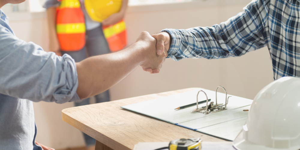 Prime contractor and subcontractor shaking hands across a table